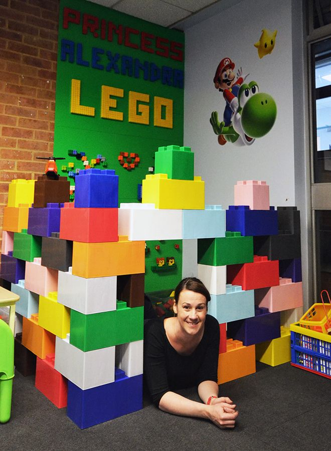 Lili Giacobino lies underneath the archway of her Lego design in the Kingston Hospital waiting room