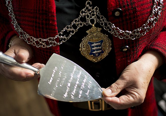 Photo of mayor holding silver trowel.