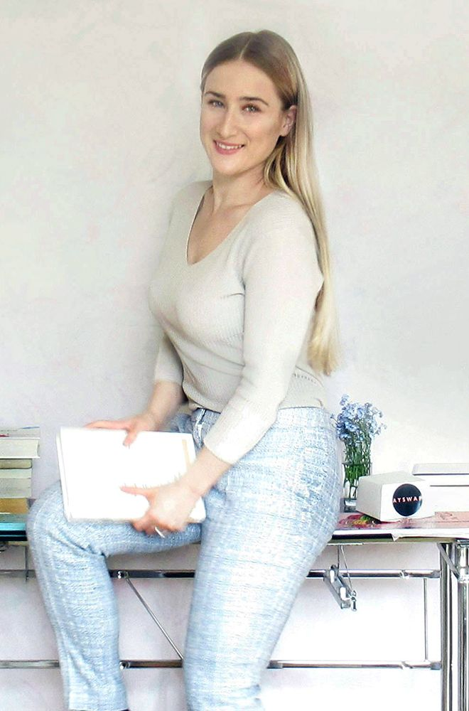 Janja Popovic sitting on a table holding a book
