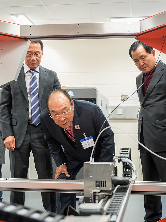 Three men examine a 3D printing machine