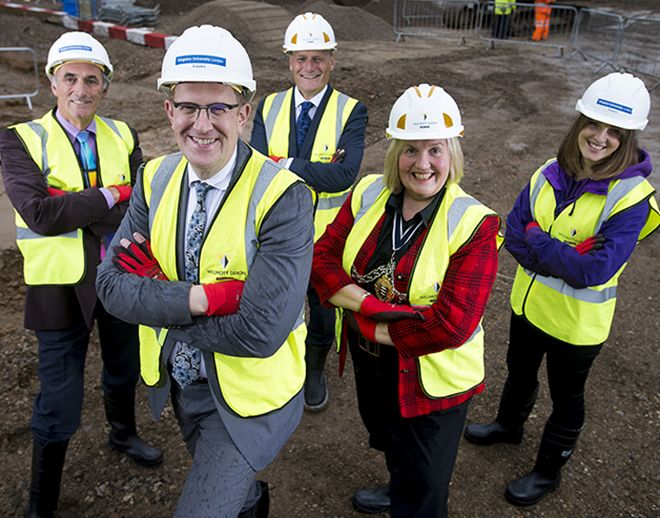 Picture of three men and two ladies in safety wear on the Town House building site.