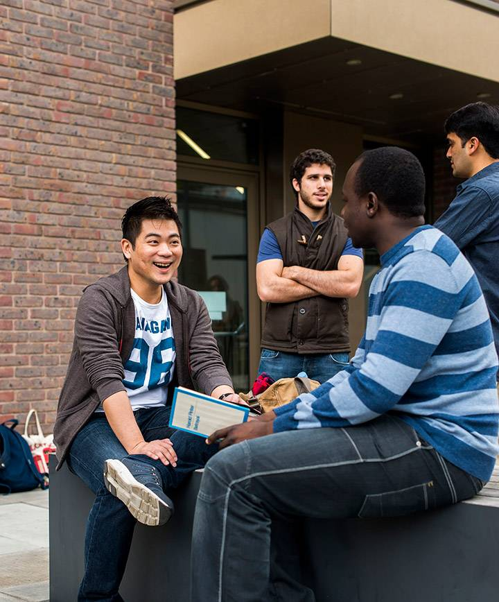 Postgraduate students outside the Business School building