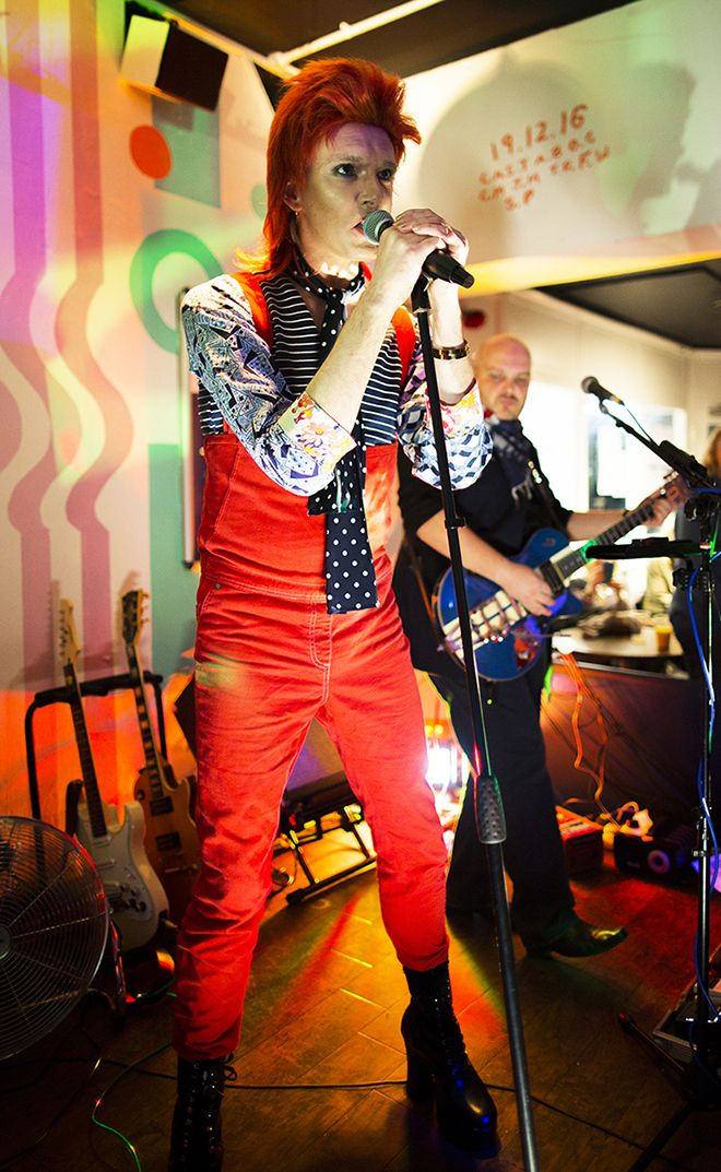 Photograph of Professor Will Brooker dressed as Ziggy Stardust singing at the David Bowie celebration gig