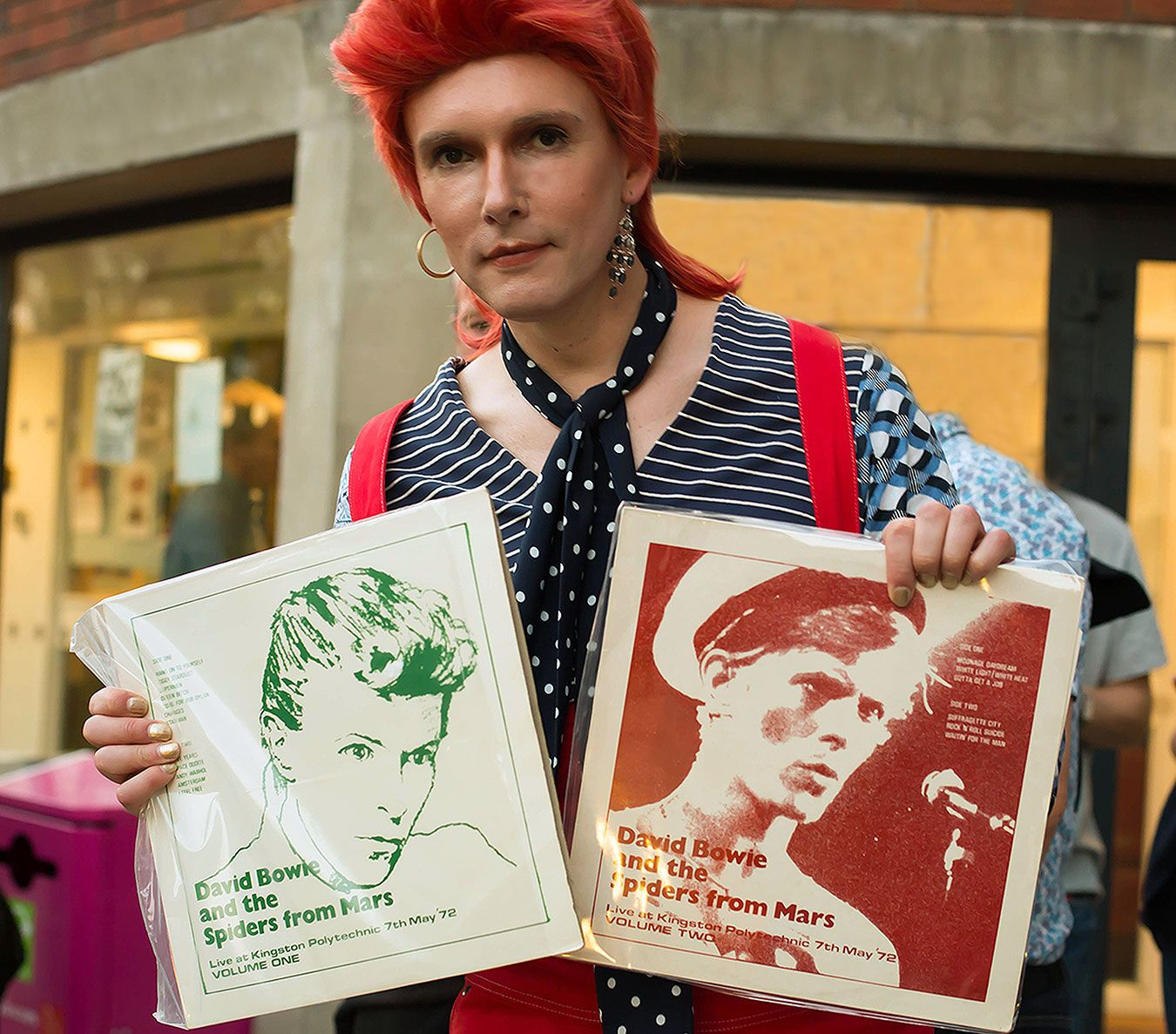Picture of Professor Will Brooker dressed as Ziggy Stardust holding two bootleg albums from the original Penrhyn Road gig