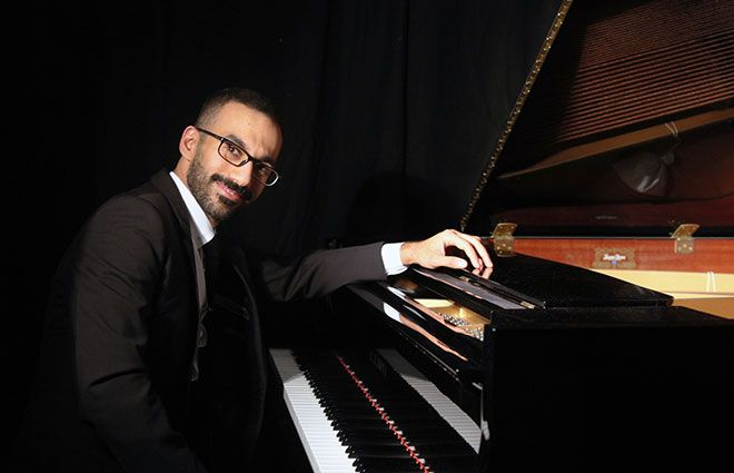 Abdullah Khalaf sitting by a grand piano