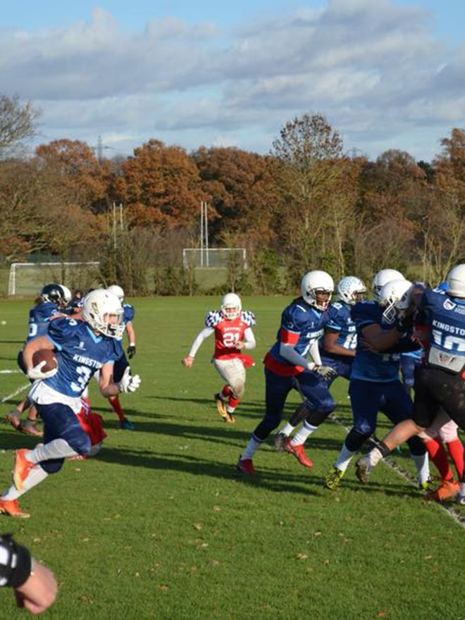 American football players scrummage for the ball
