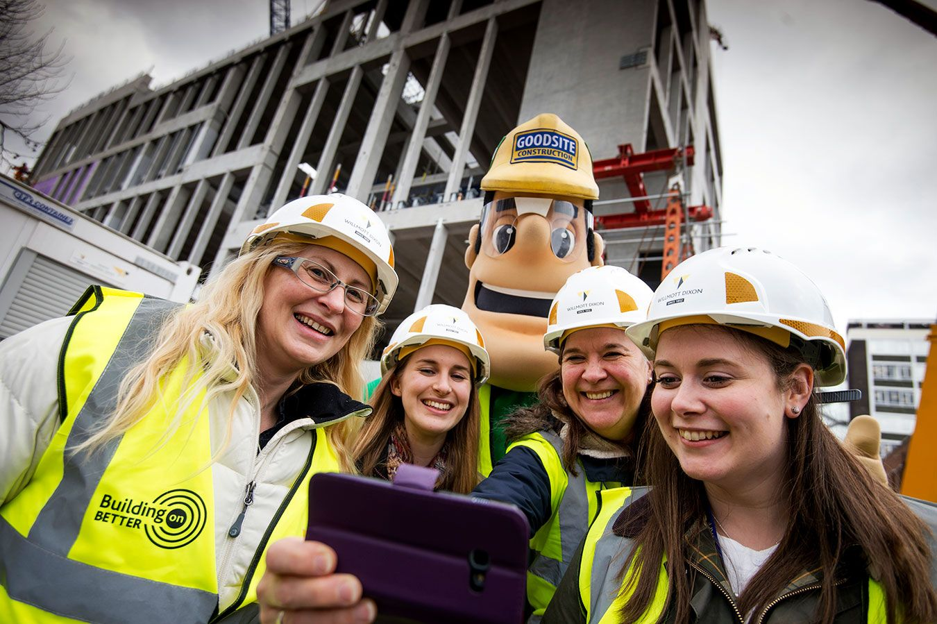 A photo of a group of people and construction industry mascot Ivor Goodsite in front of Town House
