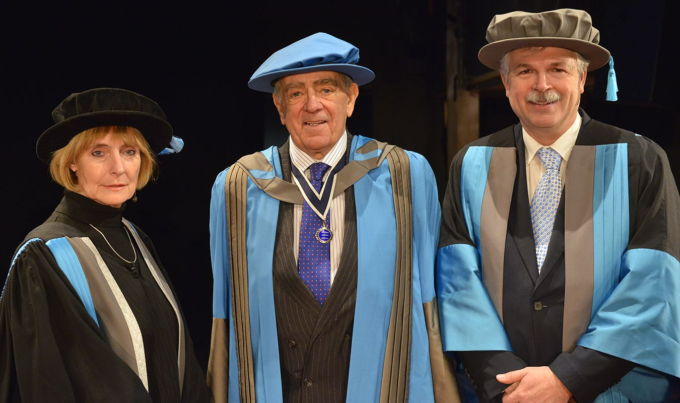 Colonel Godbold stands between Professor Anne Boddington and Professor Ron Tuninga in his graduation robes