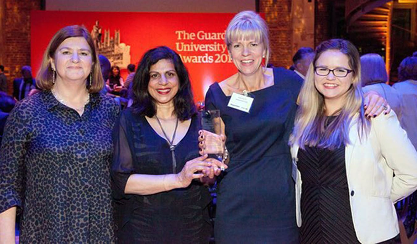 Picture of four ladies with one holding a Guardian University Award trophy.