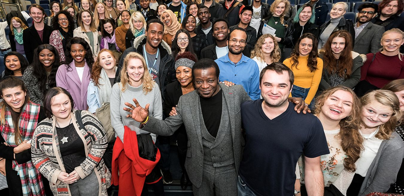 Picture of comedian Stephen K Amos surrounded by students at the 2015 media Summit.