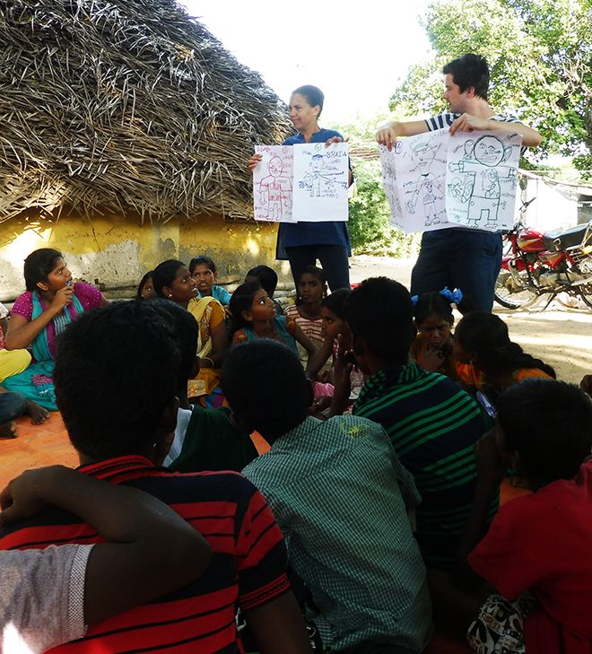 Picture of two staff members holding up pieces of paper while teaching Indian school children.