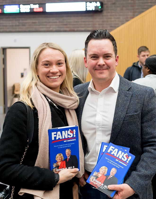 A photo of a man and a woman holding up Vernon Hill\'s book at the Strategy into Practice seminar.