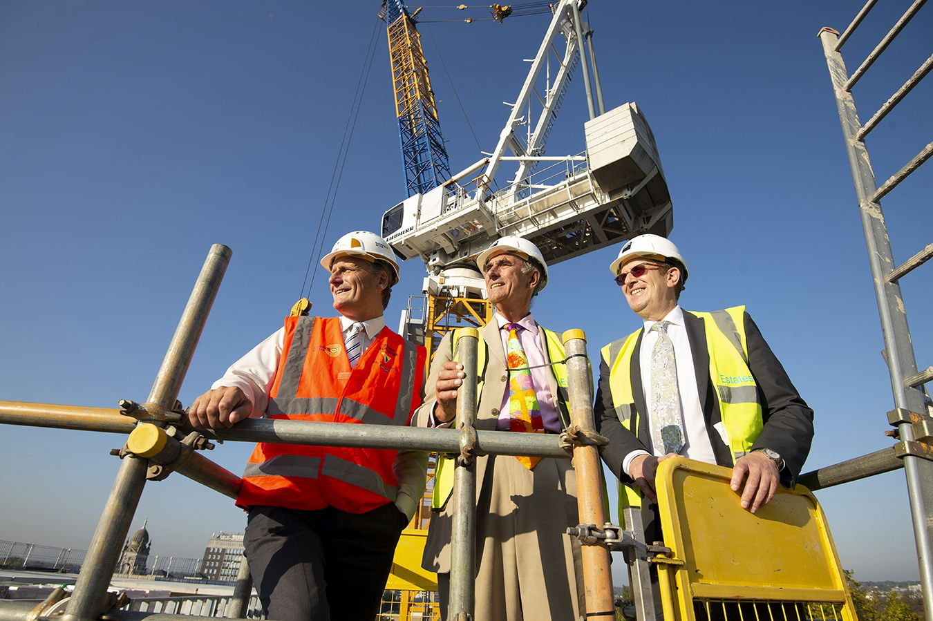 A photo of Steven Spier, David Edmonds and Roger Forsdyke at the top of a building in hard hats.