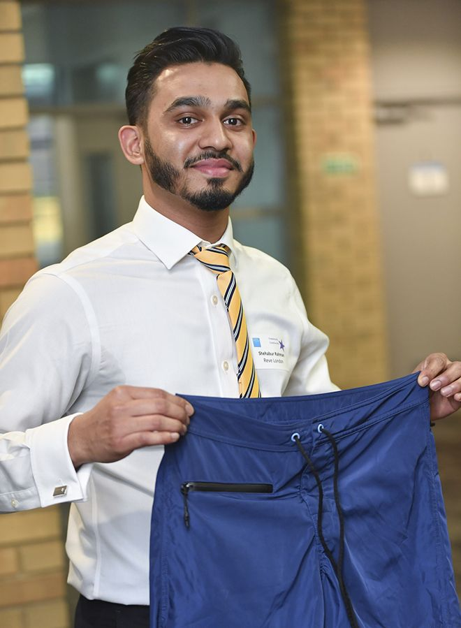 Kingston University student Shehabour Rahman holds a pair of swimming shorts with water resistant pockets