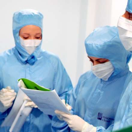 Group of students wearing overalls in sterile lab