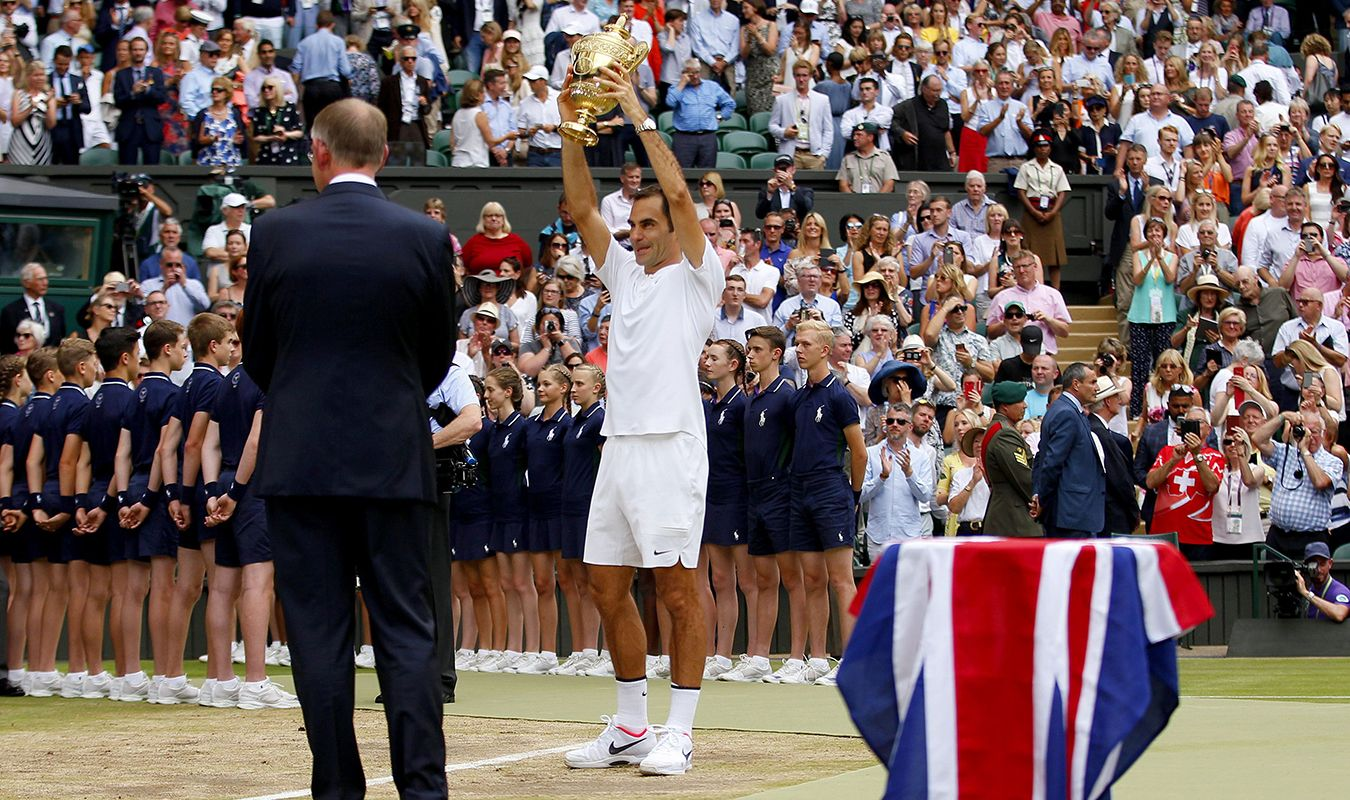 Roger Federer stands with Wimbledon tennis trophy on front of crowd