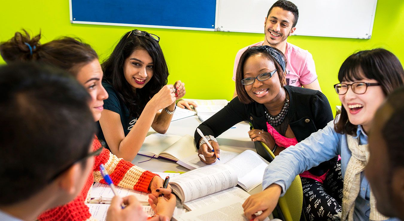 A photo of a number of Kingston University students in a discussion around a table.
