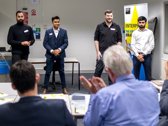 Four male students pitch their idea to a panel of judges