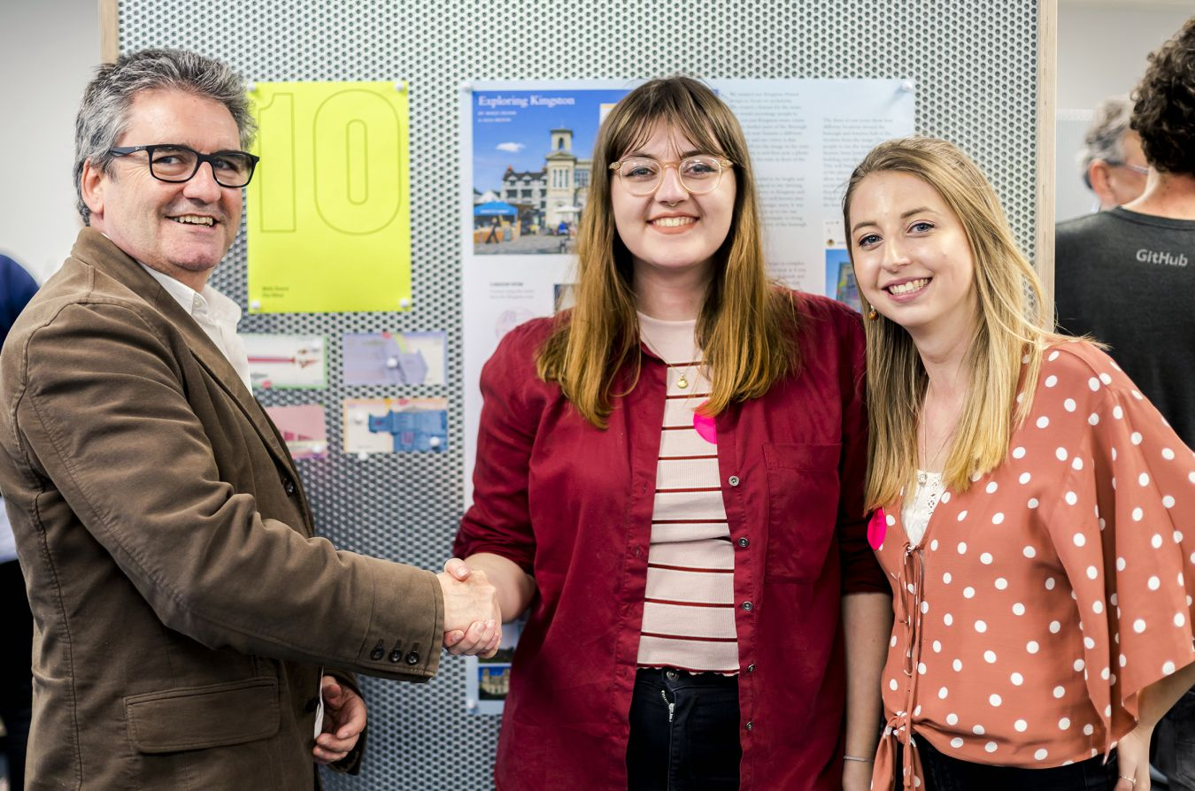 Co-founder of the Kingston Pound, Andrew Connolly, congratulates winning designers Molly Dunne and Ella Hilton.