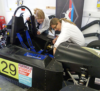Student Sabine Brosch, left, and lecturer Gordana Collier make adjustments to the electric racing car in the laboratories at the Roehampton Vale campus.