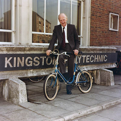 Len Lawley on a bicycle in front of Kingston Polytechnic sign