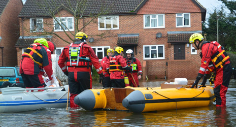 Emergency responders prepare to help another flood-stricken household in Chertsey.