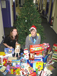 Kingston University Students' Union representative Becky Pearson, left, and Mark Callaby, right, get in the festive spirit surrounded by presents being donated to youngsters at CHASE hospice.