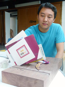 Yanchee with the prototype he produced to test his shelf design.